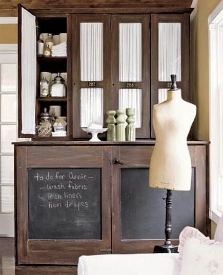 hidden laundry spaces - washer dryer in wood stain cupboard with chalkboard doors from Country Living via Atticmag