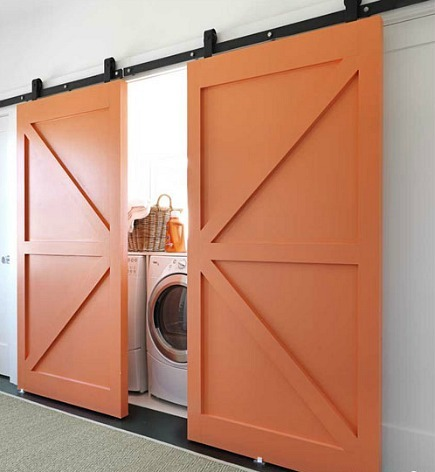 hidden laundry spaces - pumpkin orange barn doors hiding laundry room from House Beautiful via Atticmag