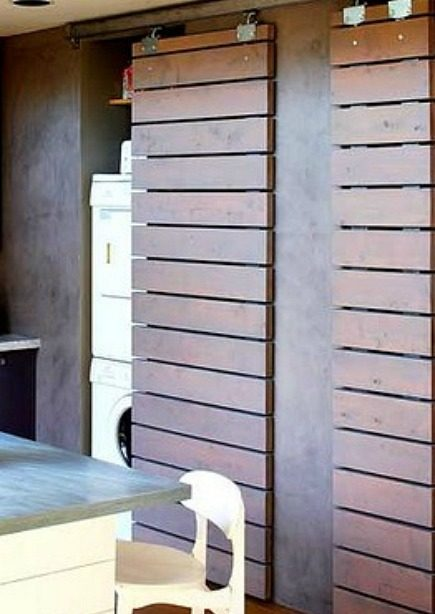 hidden laundry spaces - modern louvered sliding doors hide laundry closet from Sunset via Atticmag