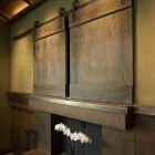 tv barn doors - sliding interior barn doors cover a flat screen tv - Schmidtt+ Co. via Atticmag