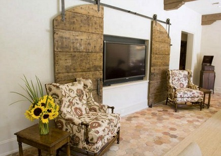 tv barn doors - full size sliding interior barn doors conceal large flat screen tv - remodelista via Atticmag
