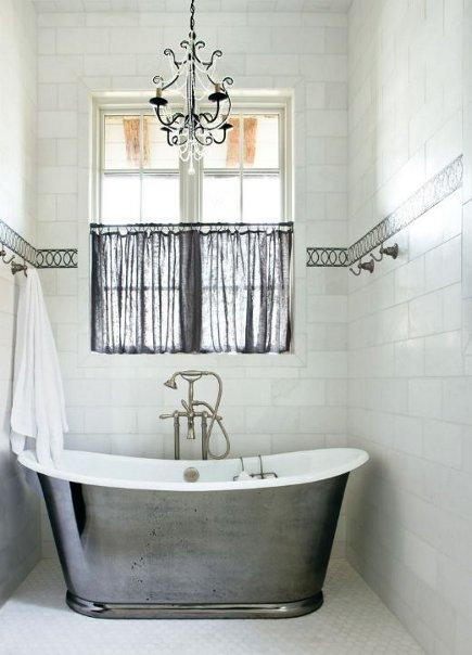 silver bathtub - in a white-tiled niche with gray accents - atlantahomesmag.com via Atticmag