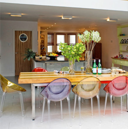 chair color - Kartell Mr. Impossible mixed color chairs around a wood dining table - clear magazine via atticmag