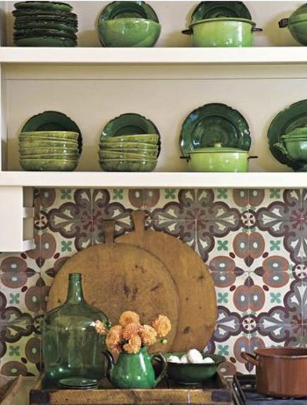 patterned tile backsplashes - antique French patterned cement tile in rustic brown and green with vintage French faience pottery - House Beautiful via Atticmag