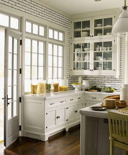white kitchen with black kitchen cabinet hardware and dark matching tile grout - pinterest via Atticmag