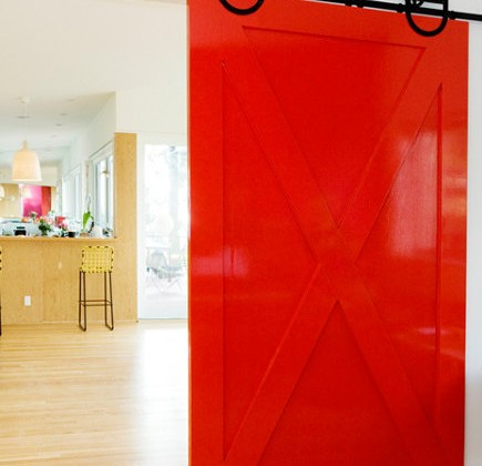 Red lacquer interior barn door in a home by by Barbara Bestor via Atticmag