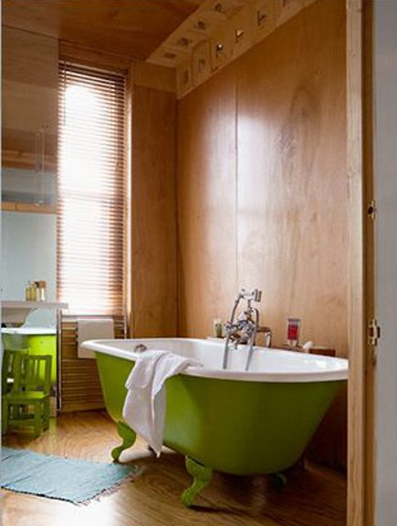 green bathroom accents - wood-paneled bathroom with clawfoot tub painted acid-green on the exterior - Paul Raeside via Atticmag