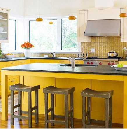 lemon yellow kitchen - yellow base cabinets and yellow and white pattern tile backsplash - BH&G via Atticmag