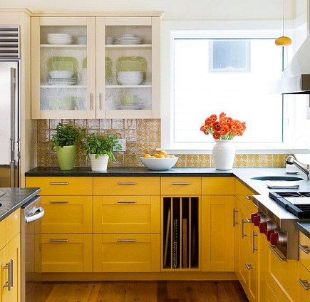 lemon yellow kitchen - yellow cabinets and yellow and white pattern tile backsplash with cream colored upper cabinets and a Wolf rangetop - BH&G via Atticmag