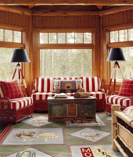 designer log cabin - master bedroom sitting area of an Idaho timber vacation home with red, green and blue winter theme decor by Anthony Baratta - AD via Atticmag