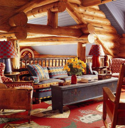 designer log cabin - upstairs landing sitting area of an Idaho timber vacation home with red, green and blue winter theme decor by Anthony Baratta - AD via Atticmag