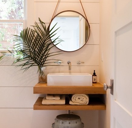 vanity shelves - vessel sink installed on an oak slab vanity shelf in a powder room - Pacific Family Homes via Atticmag
