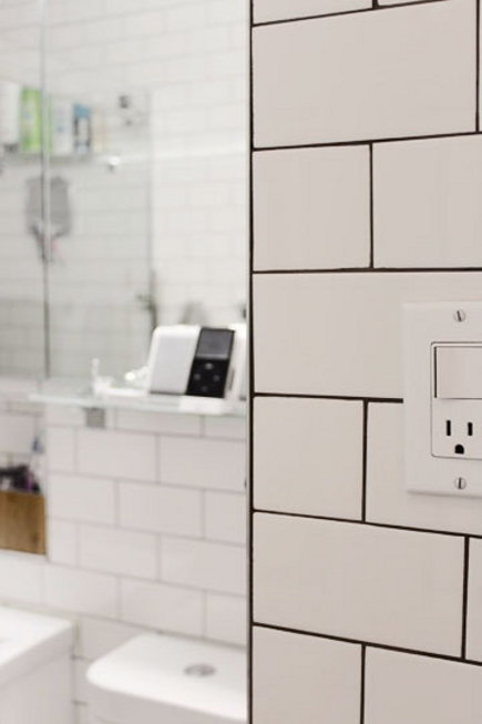 bold tile grout - close up of white glazed subway tile with black grout - apartment therapy via atticmag