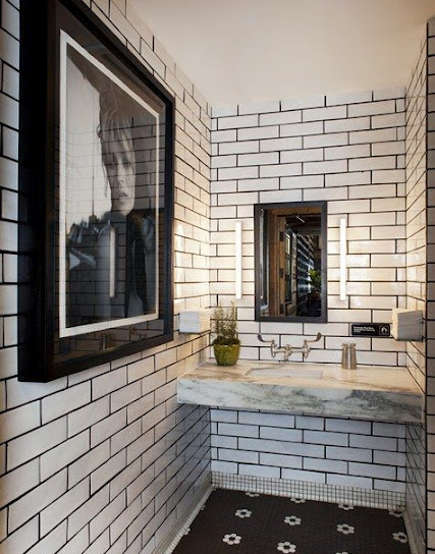 bold tile grout - restaurant bathroom with dark-grouted white subway tile and a black and white hex tile floor - desire to inspire via atticmag
