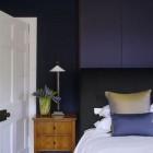 dark bedrooms walls - blue-violet walls and upholstered headboard - John Minshaw via Atticmag