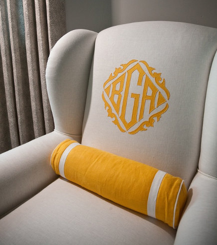 monogrammed easy chairs - white upholstered wing chair with contrasting saffron color monogram - Andrea May via Atticmag