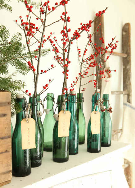 Christmas berry decor - berry branches in green-glass bottles on a mantel - French larkspur via atticmag