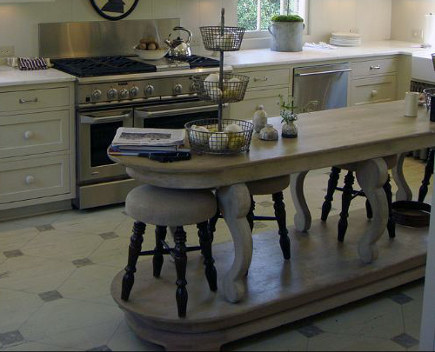 Oval shaped table and kitchen island variation on a platform with low stools - Bill Litchfield via atticmag