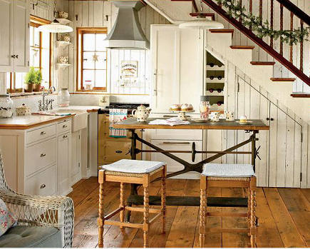 country style kitchen with yellow aga and salvaged cast iron table used as a kitchen island variation - coastal living via atticmag