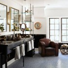 bathroom ideas - large bath with vintage upholstered seating and an antique vanity and clock - elledecor via atticmag