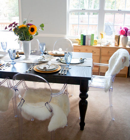 IKEA faux shearling area rugs on Ghost chair seats in dining room - Glitter and Goat Cheese via Atticmag