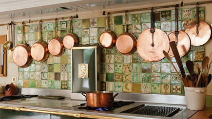 special kitchen features - utensil rails hung over a backsplash behind a range - Molteni via atticmag