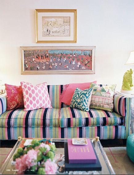 velvet striped sofa with an eclectic assortment of pillows in a studio apartment by Elizabeth Bauer - via atticmag