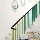 colorful painted staircase - white staircase with multicolor green spindles - terrys fabrics via atticmag