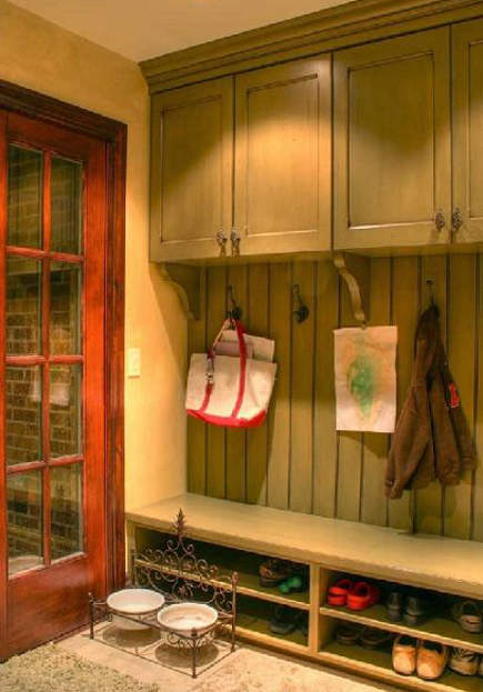 mudroom storage - painted green with double shoe storage shelves and upper cabinets,.