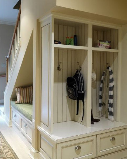 mudroom storage - hanging storage constructed behind a staircase. Case Design via Atticmag