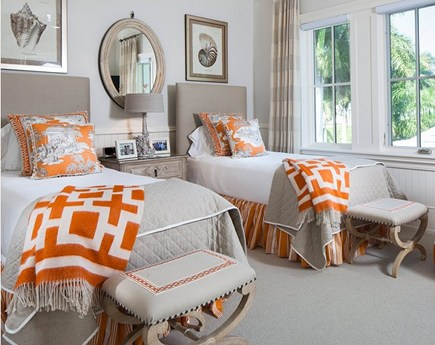 gray guest bedroom with orange accents by Joy Tribout via Atticmag
