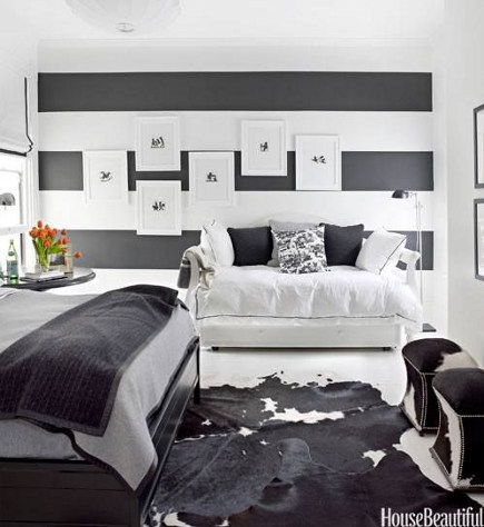 horizontal striped walls in a bedroom layered with pictures - house beautiful via Atticmag