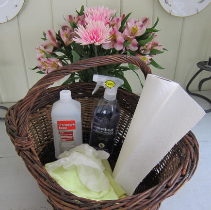 spring cleaning tips - basket of cleaning supplies including alcohol, surface cleaner, microfiber towels and paper towels - Atticmag