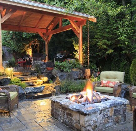 backyard built in ideas - stone firepit on a patio – alderwood landscaping via atticmag