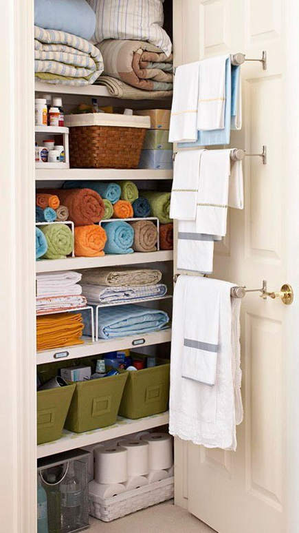 linen closet organization - decorative linen closet with hanging towel bars - bh&g via atticmag
