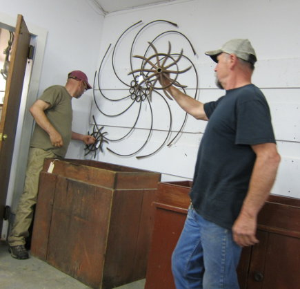 old farm implement wheel as a wall accessory at a country auction - Atticmag