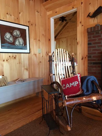 Amish made rocker and vintage bench near the fireplace at the lake camp cottage in Maine - Atticmag