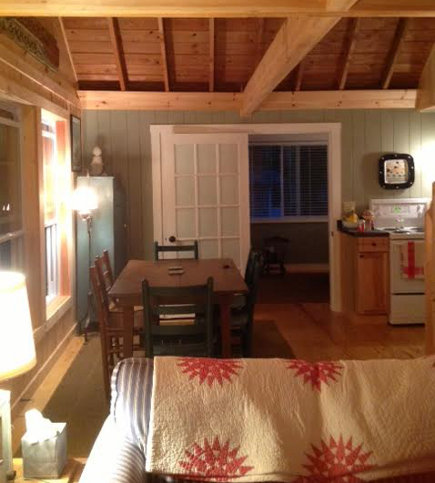 view of the dining area opening into the lake camp cottage kitchen in Maine - Atticmag
