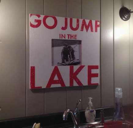go jump in the lake sign in the kitchen of a lake camp cottage in Maine - Atticmag