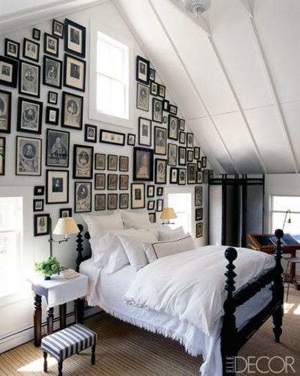 attic bedroom accent wall - master bedroom with antique photos on bed wall - elledecor via atticmag