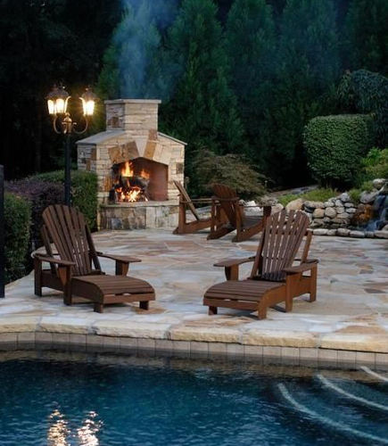 outdoor stone fireplaces - fireplace with low hearth on a poolside patio - arnold masonry and landscape via atticmag