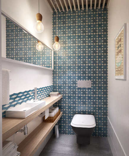 bathroom accent wall - blue and white geometric pattern tile on a commode wall - architizer via atticmag