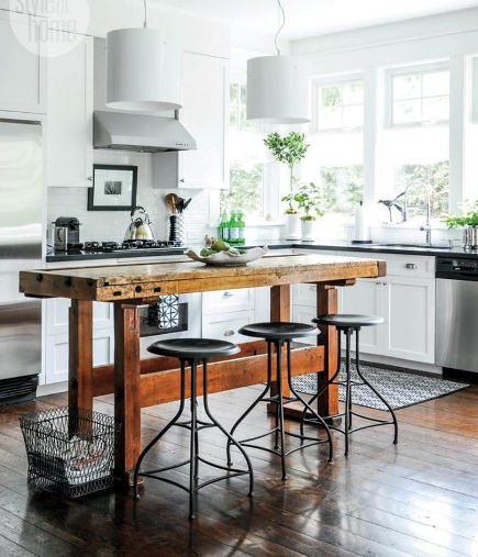 updating white kitchens - white shaker cabinet kitchen with antique wood workbench island - style at home via atticmag