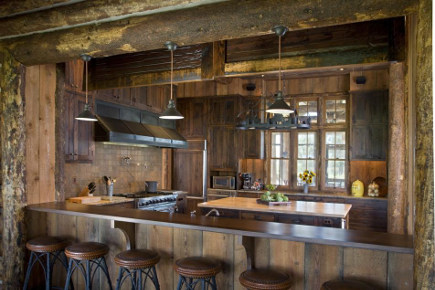 contemporary ranch kitchen - view into dark log cabin kitchen with four sided island from open pass through over the sink - onsitemanagement via atticmag