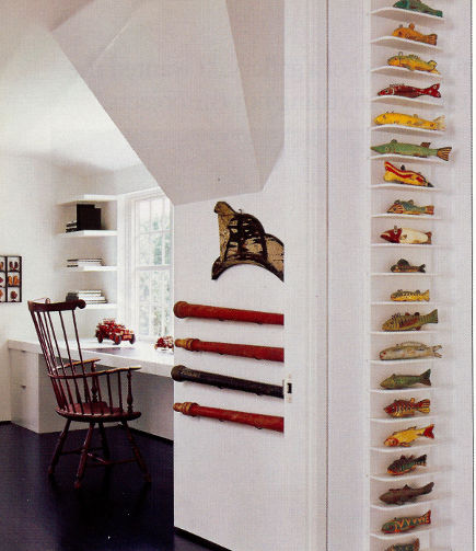minimalist gallery style displays of antique American spear fishing decoys on vertical shelves - - Architectural Digest via Atticmag