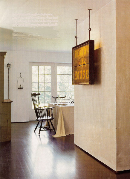 minimalist gallery style displays - an antique wooden sign is suspended from the ceiling in front of a wall - - Architectural Digest via Atticmag