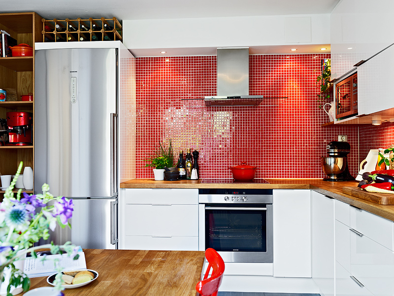red backsplash in glass mosaic tiles done as a eurosplash in Swedish apartment kitchen - stadshem.se via atticmag