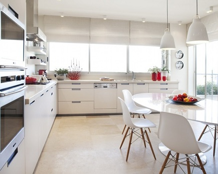 kitchen dining tables - mid-century modern white kitchen with Saarinen oval dining table and Eames while molded dowel leg chairs - Bill Litchfield Design via Atticmag