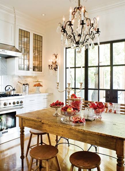 kitchen dining tables - vintage tavern table with stools and a wood-slat and iron bench in a white kitchen - Canadian House & Home via Atticmag