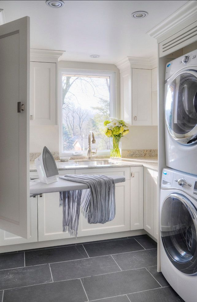 laundry room with drop-down ironing board built into a cabinet - braams custom cabinets via atticmag